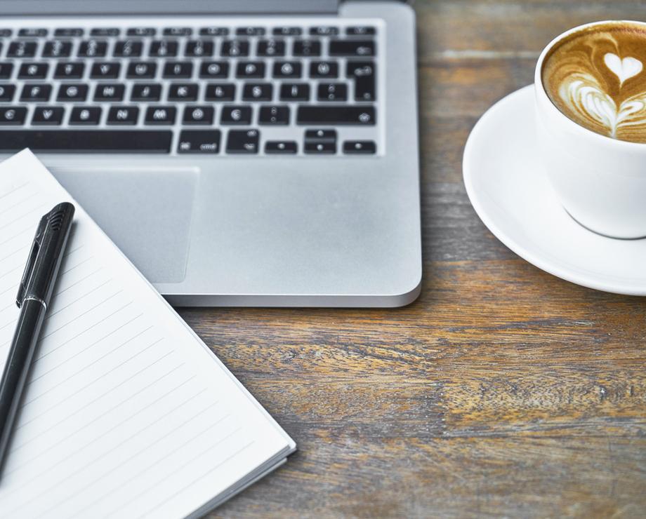 Dator, block, penna och kaffe för att skriva texter